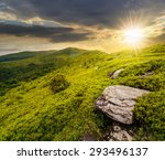 mountain landscape. valley with stones in grass on top of the hillside of mountain range in evening light - stock photo