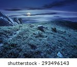 path through hillside with huge white sharp boulders near mountain peak at night in full moon light - stock photo