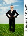 serious businesswoman standing at the green field - stock photo
