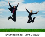 two happy colleagues jumping at the green field - stock photo
