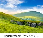 view on high mountain peak from hillside covered with white boulders and conifer trees among green grass in morning light - stock photo