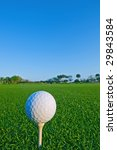 golf ball on tee against clear blue sky in florida - stock photo
