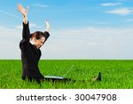 successful businesswoman with computer sitting at the green field - stock photo
