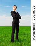 smiley businesswoman standing at the green grass - stock photo