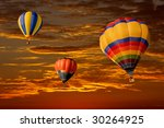 Colorful hot air balloons against a dramatic red sky - stock photo