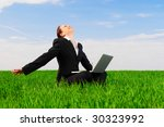 happy woman with laptop sitting at the green field - stock photo