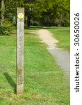 public foot path direction sign into woodland - stock photo