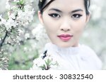 Young woman with cherry flowers. Shallow dof effect. - stock photo
