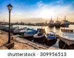 small fishing boats and few big one docked near embankment in port of Bulgarian town Sozopol in evening light - stock photo