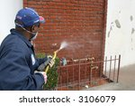 an unidentifiable person cleans graffiti off a wall in the Urban Jungle called  Los Angeles - stock photo