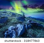 white sharp boulders on the grassy hillside on the peak on high mountain range at night in full moon and Northern Lights. composite landscape - stock photo