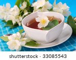 jasmine tea in white cup on blue background - stock photo