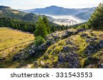 view from a rocky cliff to full of fog valley with conifer forest in high mountains of Apuseni Natural Park in Romania - stock photo