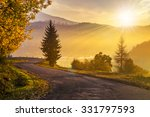 Curve old asphalt road to village in foggy mountains near the forest in evening light - stock photo