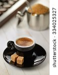 Black cup of espresso and two pieces of sugar on wooden plank table - stock photo