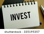 Invest memo written on a notebook with pen - stock photo