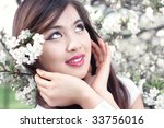 Young woman with cherry flowers. Bright white colors. - stock photo