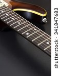 Closeup of a sunburst electric guitar with shallow depth of field on black and with copy space - stock photo