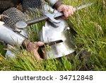 Knight's helmet and sword / wet after rain - stock photo