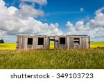 Old Decrepit Boxcar in Canola Field with Blue Sky and Clouds - stock photo