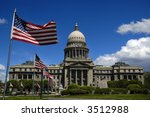 State capitol building with flags and sky - stock photo