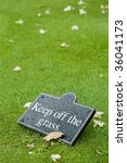 keep off the grass sign on a leafy lawn - stock photo
