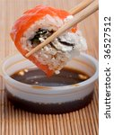 Dip california sushi roll in the soy sauce - stock photo