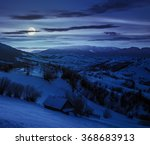 few houses of village on hillside in mountain area at night in full moon light - stock photo