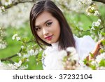 Young woman with cherry flowers portrait. - stock photo