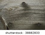 A close-up background photo of wood grain and screws in neutral tones. - stock photo