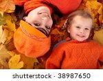 Happy family with child on autumn orange leaf. Outdoor. - stock photo