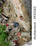 An eager female climber on a steep rock face looks for the next hold - viewed from above.  Shallow depth of field is used to isolated the climber.  A belayer and other climbers look on in anticipation - stock photo