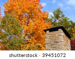 Detail of a park shelter chimney with autumn foliage - stock photo