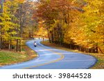 A motorcycle (with a bit of motion blur from its speed) rides through an autumn wonderland - stock photo
