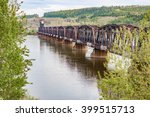 A portrait view of a rusty railway bridge across the Fraser River in British Columbia - stock photo