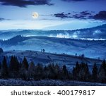 coniferous forest on hillside meadow with fog over rural  valley in autumn mountains at night in full moon light - stock photo