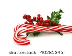 christmas candy canes with a branch of holly on a white background - stock photo