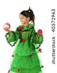 Little smiling girl in green Christmas tree costume with two Christmas decorations - stock photo