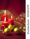 Christmas decoration with candles and ribbons / red and golden - stock photo