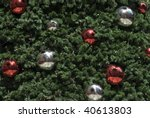 An artificial Christmas tree background with red and silver metallic baubles - stock photo