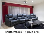Four black executive leather home theater chairs with wine glasses on tray on black table and red curtains - stock photo