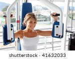 Woman at the gym doing arms exercises on a machine - stock photo