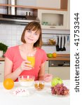 Young woman drinking orange juice with cereal muslin at home - stock photo