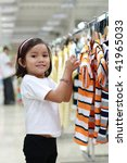 little asian cute girl shopping for a shirt - stock photo