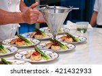 Professional chef preparing a gourmet meal as part of a catering operation. - stock photo