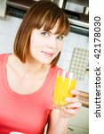 Young woman drinking orange juice at home - stock photo