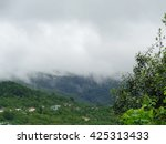 Fog over green hills and mountain village - stock photo