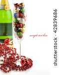 Champagne glass filled with colorful holiday ornaments, bottle of champagne and christmas decoration over white - stock photo