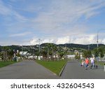 Sochi Olympic Park, palm trees and green lawns, people on footpaths, mountains on the horizon, Russia, June 1, 2016 - stock photo