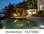 Luxurious mansion exterior at dusk overlooking pool and Bali hut - stock photo